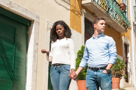 Bored disappointed African American girl holding hand of her Caucasian boyfriend. Interracial couple walking around old European city. Date or disappointed concept