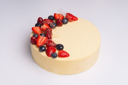 Close-up of appetizing cheesecake with berries. Tasty refreshing cake on white background. Dessert concept