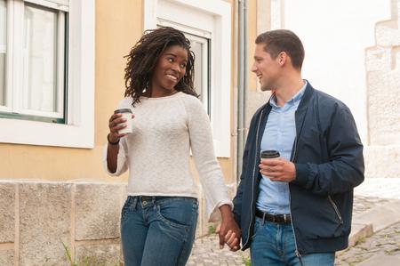 Feliz pareja interracial alegre disfrutando de la fecha. Chica afroamericana y su novio caucásico tomados de la mano, caminando por la ciudad vieja y disfrutando de un descanso para tomar café. Concepto de amor y ocio