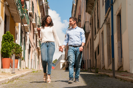 Happy cheerful mix raced couple of tourists walking through old European city. African American girl and Caucasian guy holding hands, chatting and laughing. Multicultural relationship concept