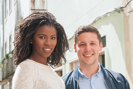Happy multicultural couple posing outdoors. Closeup of Caucasian man and black woman in casual standing in alley and smiling at camera. Multiethnic couple concept