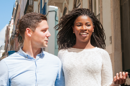 Happy multiethnic couple of tourists walking down street. Joyful African American girl and her positive Caucasian boyfriend dating outdoors. Diversity concept Stock Photo