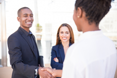 Happy African American male manager shaking hand of female partner. His female colleague standing nearby and smiling. Partnership concept Imagens - 124669481
