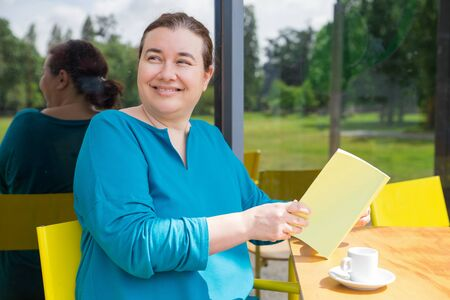 Cheerful middle aged lady spending her morning in coffee shop. Smiling Caucasian woman sitting in street cafe, holding open book and looking at somebody away. Book and coffee concept