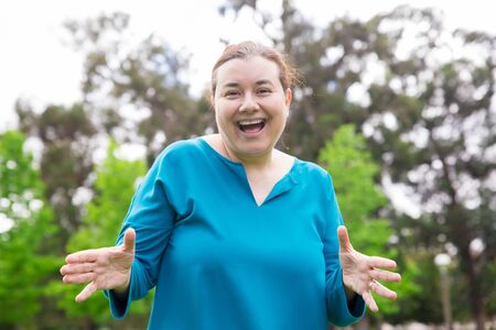 Cheerful plus sized lady having fun in park. Happy excited Caucasian woman in casual gesturing and smiling at camera. Positive emotion concept