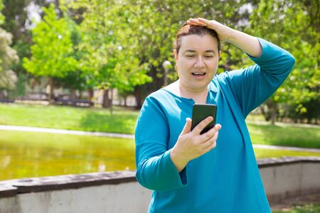 Excited middle aged woman staring at mobile phone screen with open mouth. Surprised Caucasian lady using cellphone in park, getting shocking or amazing news. Communication or surprise concept 写真素材