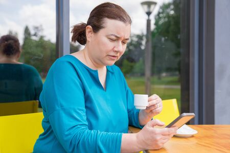 Focused frowning woman staring at mobile phone screen. Middle aged Caucasian lady using smartphone while drinking espresso in cafe. Coffee break concept