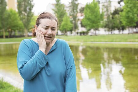 Frustrated middle aged woman suffering from toothache outdoors. Upset Caucasian lady touching cheek with pain grimace. Teeth care concept 写真素材