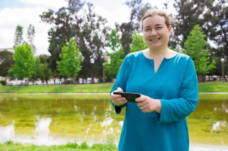 Happy peaceful woman with smartphone walking outdoors. Middle aged Caucasian lady using mobile phone app or watching videos in park and smiling at camera. Mobile internet concept