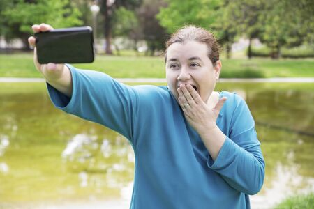 Amazed plus sized woman shooting herself in park. Middle aged Caucasian lady covering open mouth with hand and grimacing for smartphone camera or using phone for video call. Cellphone camera concept