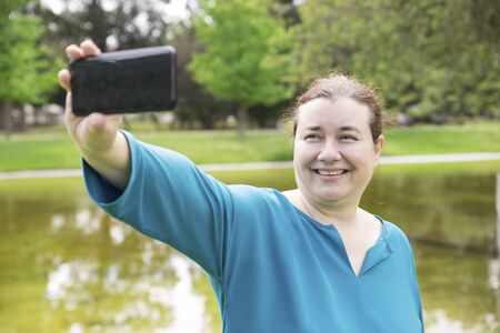 Cheerful plus sized woman taking selfie in park. Middle aged Caucasian lady enjoying leisure time outdoors and posing for smartphone camera. Self portrait concept