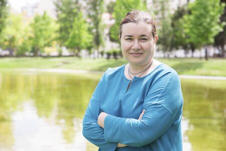 Smiling confident plus sized woman posing with crossed arms outdoors. Middle aged Caucasian lady in casual standing in park near pond and smiling at camera. Confident plus sized woman concept