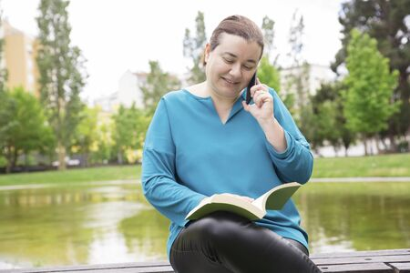 Positive middle aged student studying book and talking on cell outdoors. Smiling Caucasian lady sitting on park bench near pond, speaking on phone and reading. Multitasking concept