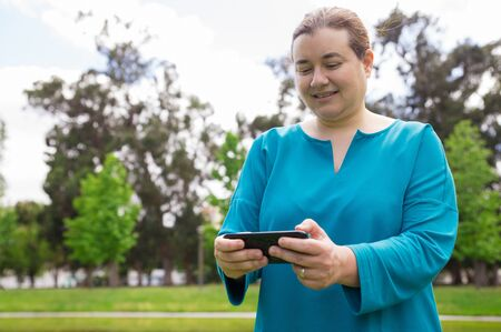 Smiling pensive woman watching media content on phone outdoors. Middle aged Caucasian lady using smartphone while walking in park. Wireless connection concept