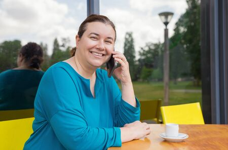 Happy middle aged lady talking on mobile phone in street cafe. Plus sized Caucasian woman speaking on cell, drinking morning coffee and smiling at camera. Coffee shop customer concept