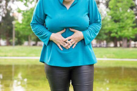 Femme souffrant de maux de ventre. Dame de taille plus debout dans un parc et touchant l'estomac. Concept de problème de santé