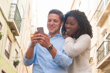 屋外で一緒にスマートフォンを使用して幸せな興奮異文化カップル。陽気な若い観光客は、市内を訪問する場所のリストを計画しています。モバイルアプリのコンセプト