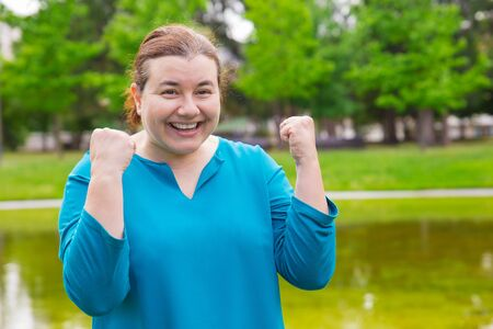 Happy excited plus sized woman celebrating success. Cheerful Caucasian lady making winner gesture with both hands and smiling at camera. Winning concept Banque d'images - 124600881