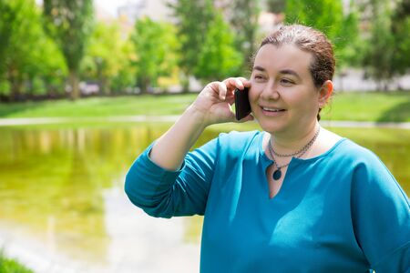 Happy focused middle aged woman excited with phone call. Positive Caucasian lady talking on cellphone in park looking away and smiling. Telephone conversation concept