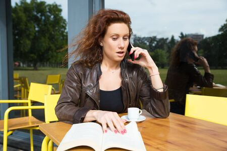 Shocked young woman getting bad news by phone. Emotional woman sitting at outdoor cafe with book and having unpleasant phone call. Communication concept 写真素材