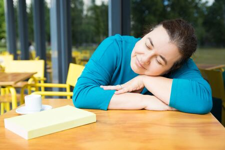 Smiling woman napping at cafe table after reading. Positive woman leaning on table with her eyes closed after finishing good novel. Books lover concept