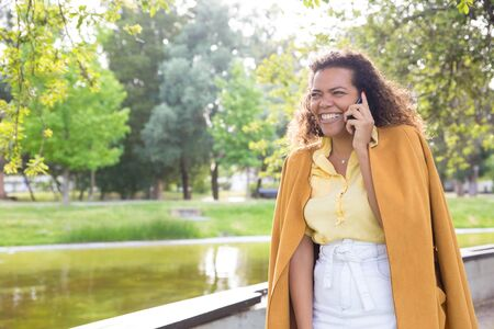 Woman talking on phone and laughing in city park. Lady with blurred trees and river in background. Summer and communication concept. Front view.
