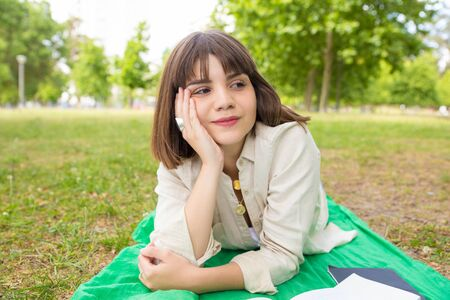 Peaceful relaxed student girl enjoying leisure time in park. Young woman lying on blanket outdoors, leaning head on hand and looking away. Leisure outdoors concept Banco de Imagens - 124922886