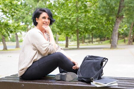 Happy satisfied woman waiting someone in park. Middle aged lady-sitting with legs crossed near bag and notebooks on bench, leaning chin on hand and staring into distance. Woman in park concept Banco de Imagens
