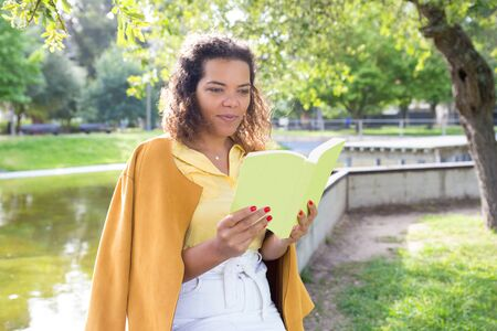 Positive young woman reading book in city park. Lady standing with blurred tree and river in background. Summer and education concept.