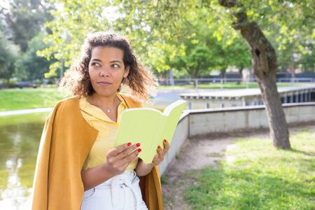Serious young woman reading book in city park. Lady standing with blurred tree and river in background. Summer and education concept.