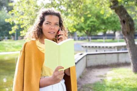 Smiling woman reading book and talking on phone in city park. Lady standing with blurred tree and river in background. Summer and education concept. Archivio Fotografico