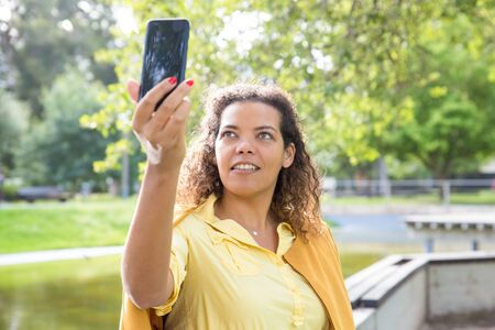 Smiling woman taking selfie photo on smartphone in park. Young woman posing with blurred green trees and river in background. Nature and selfie concept. Front view.