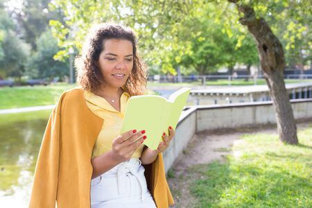 Smiling young woman reading book in city park. Lady standing with blurred tree and river in background. Summer and education concept. 写真素材