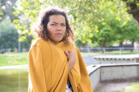Unhappy woman wrapping in coat in park. Young lady looking at camera with blurred green tree and river in background. Cool weather concept. Stockfoto