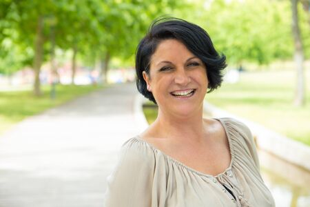 Cheerful excited woman walking in park and laughing. Mature black haired lady enjoying nature outdoors and smiling at camera. Happy woman outdoors concept