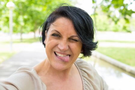 Cheerful funny woman grimacing and taking selfie outdoors. Self portrait of middle aged Caucasian lady putting out her tongue, winking and smiling at camera. Selfie and fun concept
