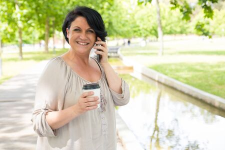 Cheerful happy lady talking on cell over cup of coffee in park. Black haired mature woman holding disposable cup, speaking on cellphone and smiling at camera. Communication or coffee break concept Stockfoto