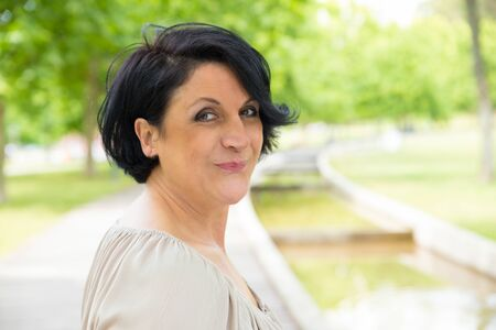 Cheerful middle aged woman enjoying walk in park. Closeup of black haired Caucasian lady turning face to camera and smiling. Happy woman in park concept