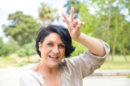Cheerful middle aged woman having fun in park. Funny Caucasian lady showing peace sign and smiling at camera. Fun outdoors concept