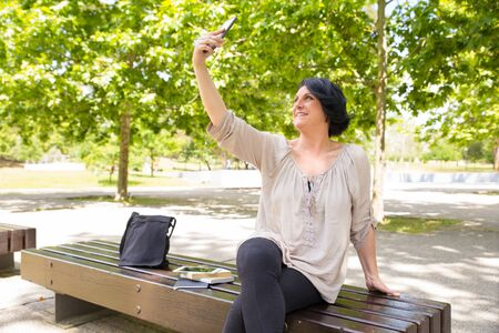 Cheerful middle-aged woman taking selfie outdoors. Happy Caucasian lady shooting herself on park bench. Photography concept 写真素材