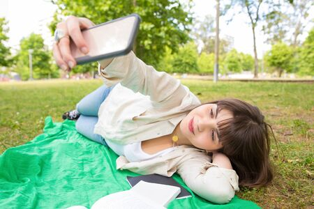 Cheerful tranquil student girl photographing herself on phone in park. Young woman lying on grass outdoors and taking selfies. Selfie concept Stockfoto