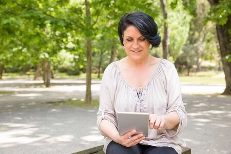 Focused smiling woman using tablet outdoors. Middle aged Caucasian lady sitting on park bench, holding gadget, and touching screen. Communication outdoors concept