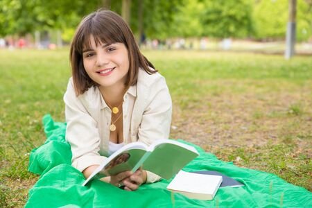 Happy beautiful student girl lying on blanket with books outdoors. Young woman enjoying book reading in park and smiling at camera. College campus concept
