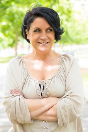 Happy black-haired woman standing for camera with arms crossed. Middle aged Caucasian lady posing in park, looking away and smiling. Outdoor female portrait concept