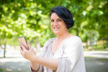 Happy relaxed woman using online app outdoors. Middle aged Caucasian lady holding smartphone, touching screen and smiling at camera. Mobile internet concept
