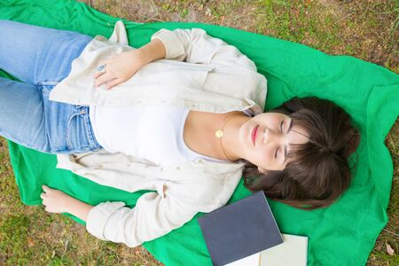 Peaceful tranquil girl relaxing in park. Top view of young woman lying on grass with closed eyes. Relaxing outdoors concept Banco de Imagens - 124922955
