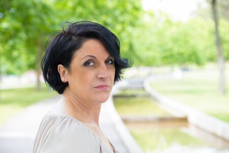 Serious confident woman in casual posing while walking in park. Closeup of middle aged Caucasian lady turning face to camera. Outdoor female portrait concept Stockfoto