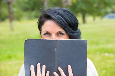 Smiling sly woman covering low face with open notebook with blank cover. Middle aged Caucasian lady reading notes outdoors, hiding face behind copybook and looking at camera. Keeping secret concept Stockfoto