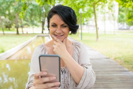 Smiling pensive lady taking pictures on smartphone in park. Middle aged woman in casual holding mobile phone, watching content and smiling at screen. Digital technology concept 写真素材