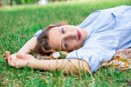 Calm young woman lying on grass and looking at camera. Content girl in shirt relaxing in city park. Laziness concept Reklamní fotografie